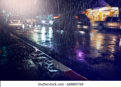 Hard rain fall at night with blurry cars as background.Selective focus.