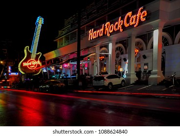 Hard Rock Cafe music club.  Fhuket, Thailand - May 28, 2016 Neon guitar and blurry car traffic in front of the Hard Rock Cafe music club in the city of Fhuket in Thailand.
