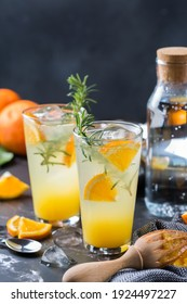 Hard seltzer cocktail with orange, rosemary and ice on a table. Summer refreshing beverage, drink on a black table