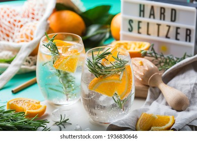 Hard seltzer cocktail with orange, rosemary and ice on a table. Summer refreshing beverage, drink with trendy zero waste accessories, bamboo straw and mesh bag.