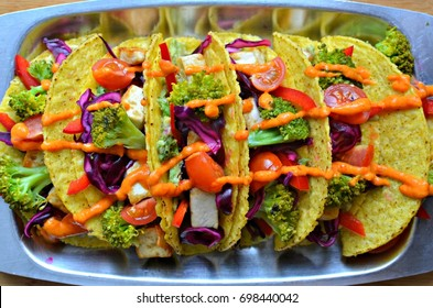 Hard shell tacos filled with tofu and vegetables, topped with a spicy salsa sauce