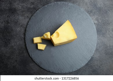 Hard sliced yellow Maasdam cheese slate blackboard on black background. Concept serving cheese. Top view, copy space.