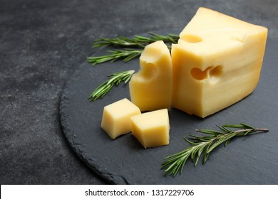 Hard sliced yellow Maasdam cheese with rosemary on slate board on black background. Concept serving cheese. Copy space.