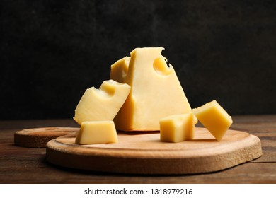 Hard sliced yellow Maasdam cheese on wooden cutting board on table on black background. Concept serving cheese.