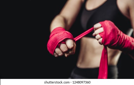 Hard sport woman ready for fight. Fighter girl in sports top, red elastic bandages fists on black background