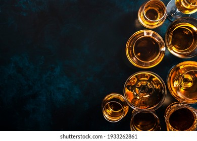 Hard strong alcoholic drinks, spirits and distillates in glasses: vodka, cognac, tequila, scotch, brandy and whiskey, grappa, vermouth, rum. Blue background, top view