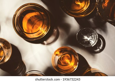 Hard strong alcoholic drinks, spirits and distillates in glasses: vodka, cognac, tequila, scotch, brandy and whiskey, grappa, vermouth, rum. White background with hard lights and shadows, top view