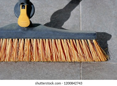 Hard surface broom with heavy duty yellow plastic bristles standing on outdoor terrace.