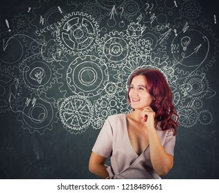 Hard thinking serious smart woman over blackboard background gear brain arrows and mess as thoughts. Concept for mental, psychological development. Finding solution to problem.