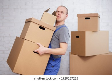 hard work concept - tired man holding many boxes in hands over white brick wall
