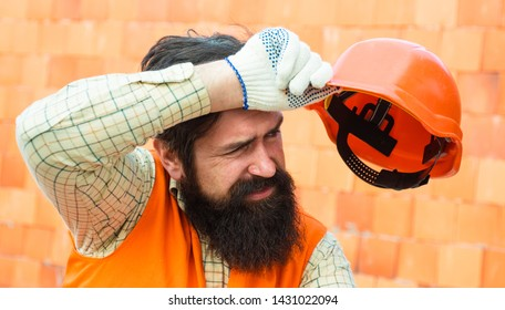 Hard work at a construction site. Heavy profession. Male builder wipes sweat from brow. Tired builder. Physical work in hot weather. Heat and safety at work.