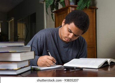 Hard working African American teenaged student, studying at home with stack of books and study materials.