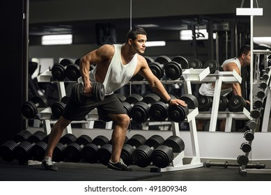 Hard working athletic man training with a dumbbell