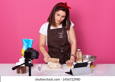 Hard working brunette housewife trying new recipe, recording video, putting rolling pin on dough, wearing brown apron, red headband and white t shirt, having tablet and camera on table. Cook concept.