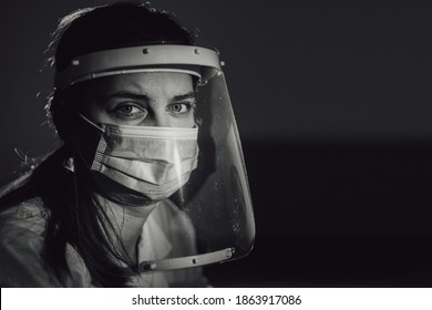 hard working female doctor, heath care worker with face shield and mask in black and white