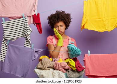 Hard working tired housewife sighs from tiredness, touches cheek, wears rubber gloves, stands near clotheslines with hanged clean clothes, feels bored of daily routine at home, does washing all day