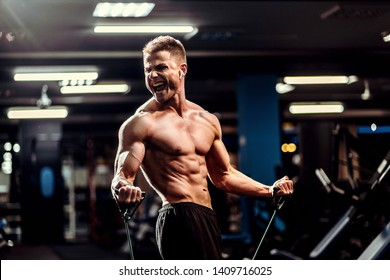Hard working well built sportsman exercising with a resistance band in gym
