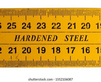 Hardened steel text written on a yellow metallic metric system ruler.