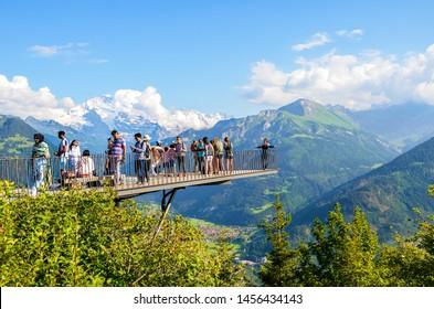 Harder Kulm, Interlaken, Switzerland - July 16 2019: Tourists taking photo on viewing platform above Swiss Interlaken. Alps in background. Beautiful mountains. People, tourism. View point