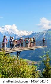 Harder Kulm, Interlaken, Switzerland - July 16 2019: People taking picture on viewing platform above Swiss Interlaken. Alps in background. Amazing mountains. People, tourism. Alpine landscape