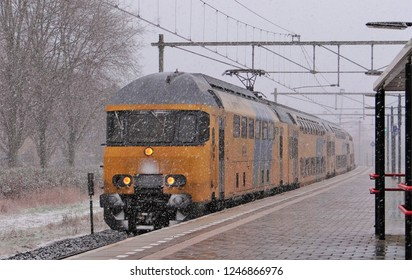 Harderwijk / Netherlands - February 8 2013: A Dutch NS train in a snow blizzard during the winter at the railway station of Harderwijk