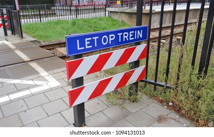 Harderwijk / Netherlands - September 25 2013: A warning sign for the railroad crossing :'Let op trein' (be careful for the train) The board has red and white stripes.