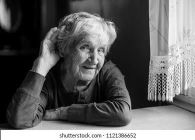 A hard-of-hearing elderly woman put her hand to her ear. Black and white photo.