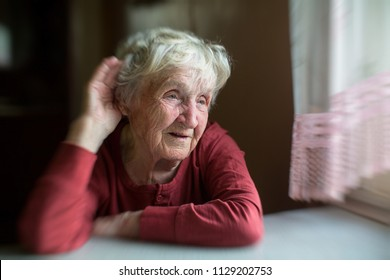 A hard-of-hearing elderly woman puts her hand to her ear, moving in a blur.