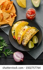 Hard-shell tacos and nachos, top view. Tortillas filled with cheese, vegetables and meat, and served with salsa dip.