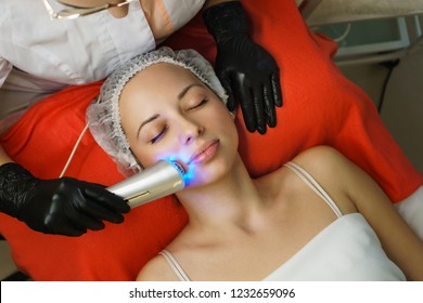 Hardware cosmetology. Beautician makes chromotherapy ultrasound cleaning the client's face. Skin pore cleansing. Anti-aging treatments. Spa. Non-invasive therapy