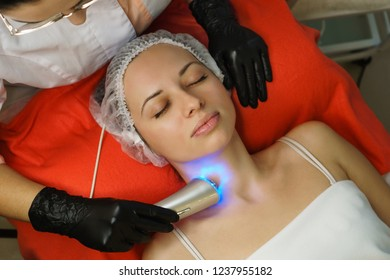Hardware cosmetology. Beautician makes ultrasound phototherapy of the client's neck. Skin pore cleansing. Anti-aging treatments. Spa. Neck area