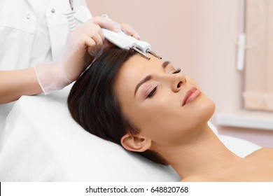 Hardware cosmetology.Spa clinic.Beautiful woman at facial treatment procedure. Microcurrent therapy.Non-surgical face lifting. Young healthy skin. Anti-aging treatment. Skin rejuvenation. Cosmetology.