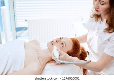 Hardware cosmetology. Close up picture of attractive woman with ginger hair and fresh freckled skin receiving rf lifting procedure in a beauty centre. Skin rejuvenation concept.