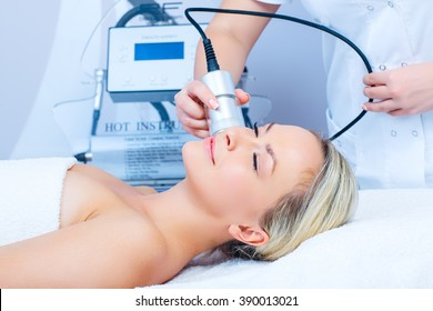 Hardware cosmetology. Closeup picture of happy young woman with closed eyes getting cryomassage procedure in a beauty parlour.
