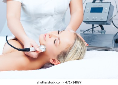 Hardware cosmetology. Closeup picture of happy young woman with closed eyes getting rf lifting procedure in a beauty parlour.