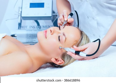 Hardware cosmetology. Closeup picture of lovely young woman with closed eyes getting rf lifting procedure in a  beauty parlour.