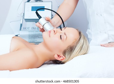 Hardware cosmetology. Closeup picture of young woman with closed eyes getting cryomassage procedure in a beauty parlour.