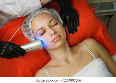 Hardware cosmetology. Cosmetologist does ultrasound phototherapy for cleaning face of client. Skin pore cleansing. Anti-aging treatments. Spa. Non-invasive therapy
