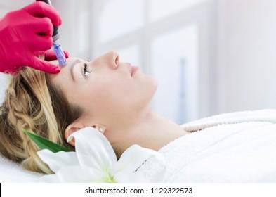 Hardware cosmetology, mesotherapy, retrato de mulher jovem que recebe tratamento de zona de testa no spa.