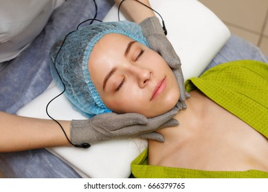 Hardware cosmetology. Microcurrents. Face rejuvenation with the help of microcurrent therapy. Facial massage with gloves with microcurrents