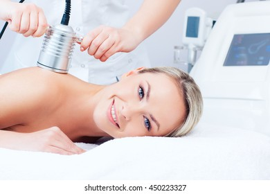 Hardware cosmetology. Picture of happy young woman getting cavitation procedure in a beauty parlour.