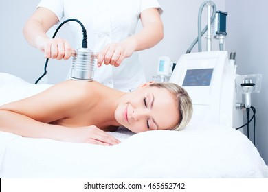 Hardware cosmetology. Picture of happy young woman with closed eyes getting cavitation procedure in a beauty parlour.