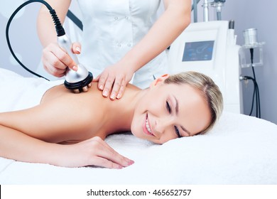 Hardware cosmetology. Picture of happy young woman getting rf lifting procedure in a beauty parlour.