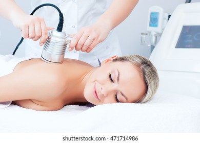 Hardware cosmetology. Picture of young woman with closed eyes getting cavitation procedure in a beauty parlour.