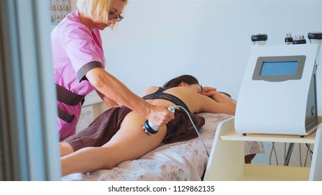 Hardware figure correction. Machine cosmetology. Anti-cellulite program for health and slimming. Apparatus massages buttocks and hips of young female.