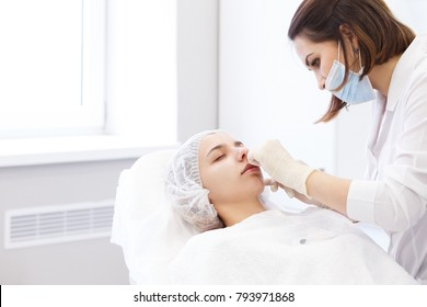 Hardware and Injections cosmetology. Process of facial beauty injections, biorevitalization of female face procedure in a beauty clinic . Cosmetologist works with patient in a white cosmetology office