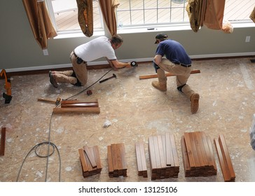 Hardwood Floor Installation - Construction workers install a hardwood floor over oriented strand board in a residence.