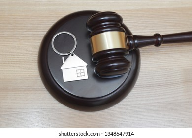 Hardwood gavel laying on sound block next to metallic key ring in shape of house. Concept of real estate auction or law.