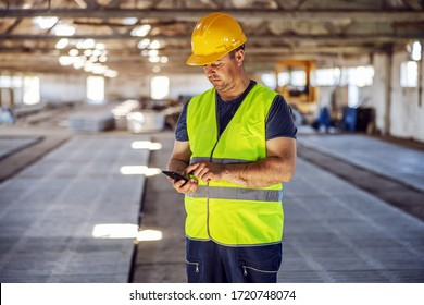 Hardworking blue collar worker standing at construction site and using smart phone to order some more materials for building.