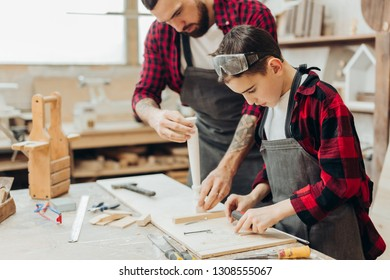 Hardworking caucasian junior school age boy holding ruler and making marks on wooden plank when his father watching over the process